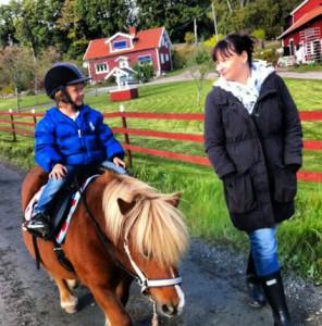 Mamma och pojke ute i naturen rider på häst. avslappnad lycka
